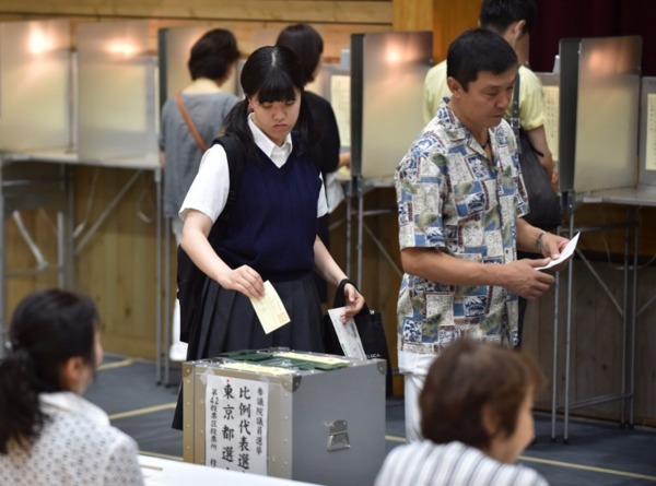 學生穿着校服投票。 (圖:AFP)
