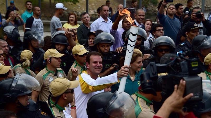 里約市長帕埃斯在民眾簇擁下傳遞聖火。 (圖:AFP)