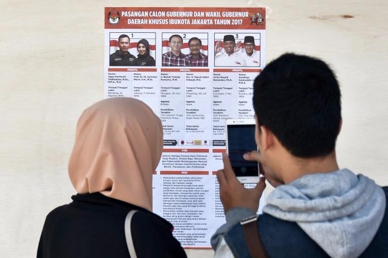 民眾在競選海報前,仔細閱覽候選人資歷。  (圖:AFP)