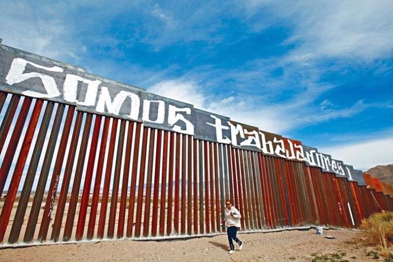 墨西哥人將示威字句塗在現有的墨美邊境圍欄上,抗議特朗普的移民改革政策。