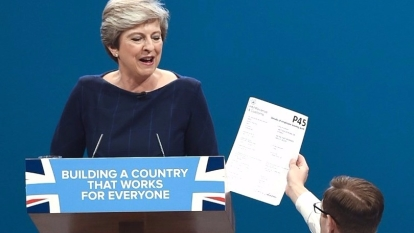 英國首相梅伊周三在曼徹斯特保守黨年會發表演說,其間一名喜劇演員走到台前將一份離職退稅表遞給她,揶揄她應下台。 (圖:AFP)