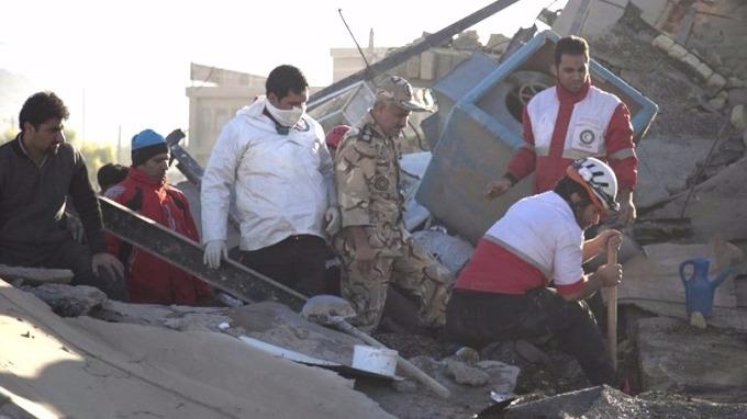 伊朗救援人員在瓦礫堆中搜尋生還者。 (圖:AFP)