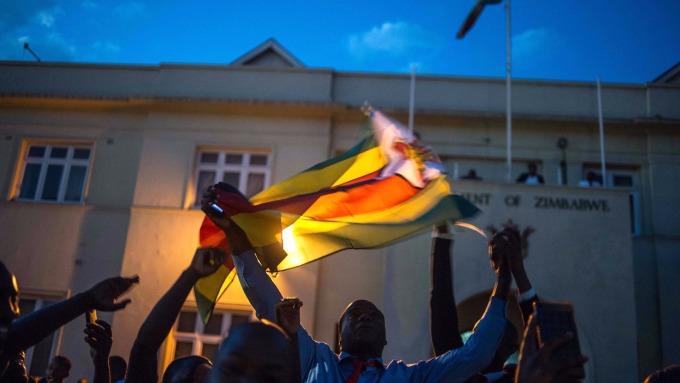 哈拉雷民眾揮舞辛巴威國旗,慶祝穆加比下台。(AFP)