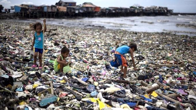 人類每年向海洋傾倒至少800萬噸塑膠垃圾。圖為兒童在海攤撿拾塑膠瓶。 (圖:AFP)