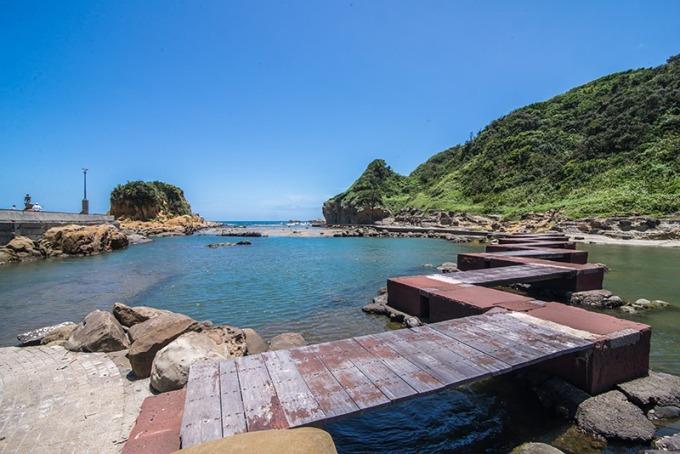 一條由石頭與木頭搭建而成閃電狀的橋延伸到對岸