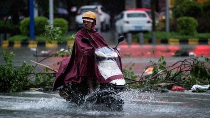 強颱「山竹」肆虐廣東,水淹馬路,騎士涉水而過。 (圖:AFP)