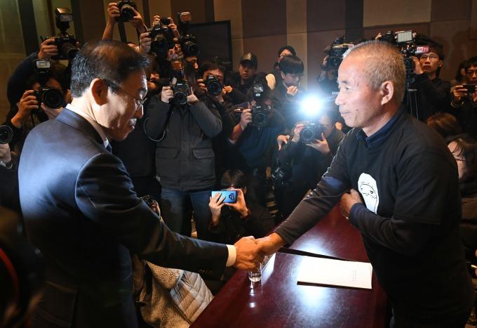 金奇南 (左) 與罹癌員工家屬黃尚基 (右) 握手和解。(圖:afp)