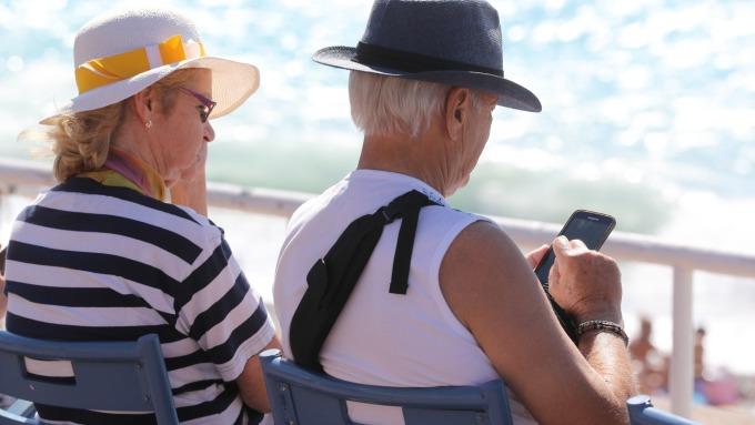 操作智慧型手機的銀髮族 (圖片來源:AFP)