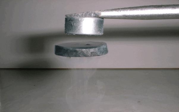 這不是魔法,而是超導體 (Superconductor) 的完全反磁現象。圖中是一高溫超導體懸浮在磁鐵之下。 圖片來源│吳茂昆提供