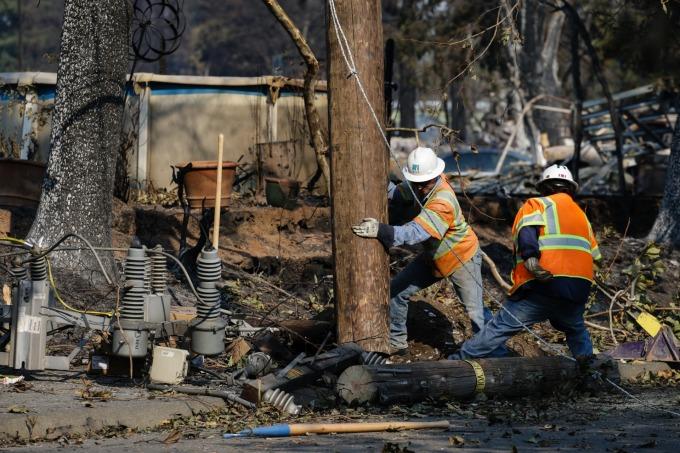 PG&E 人員在加州大火後,修繕輸電設備。(圖:AFP)