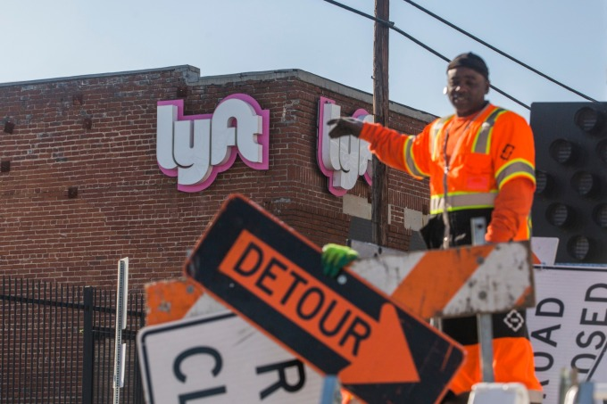 Lyft 創始人 Logan Green 和 John Zimme 以及其他公司高管,在距離納斯達克數千英里之外的洛杉磯一家前汽車經銷商處按鈕宣告上市掛牌交易。(圖: AFP)