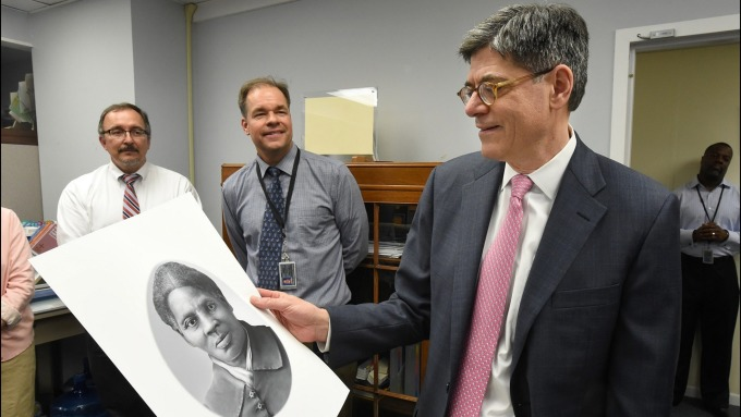 圖為歐巴馬時期財政部長Jack Lew手持塔布曼肖像 (圖:AFP)