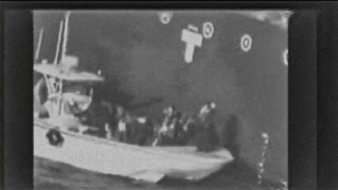 美軍公布的影像顯示,一艘巡邏艇正在拆除遇襲油輪船身上的未爆水雷。(圖片:AFP)