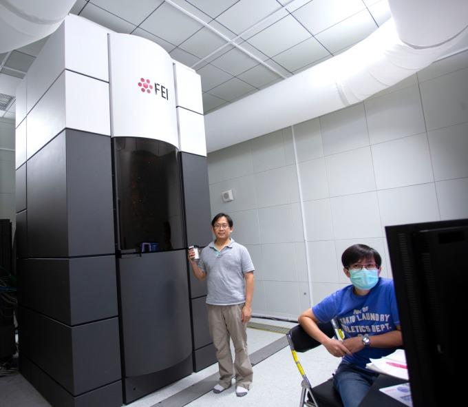 中研院的一台高階冷凍電子顯微鏡:Titan Krios。為了不干擾冷凍電顯的觀測,整個環境設計為防震、吸音、控溫、控濕,一絲絲微風也沒有。圖中立者為中研院生化所副研究員何孟樵, 坐者為冷凍電顯中心經理張淵智。 攝影│林洵安