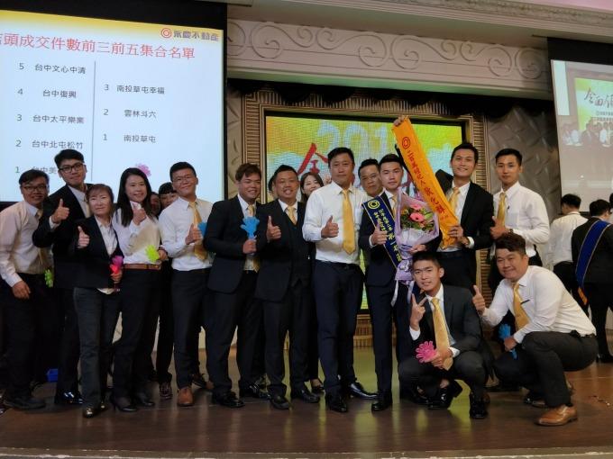 來自信義房屋的孫堙炘店東(後排右2),1年內成立2間永慶不動產加盟店,帶領著一群八年級的同仁創下傲人成績。