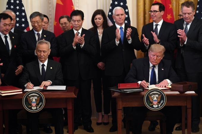 美國總統川普與中國國務院副總理劉鶴代表簽署第一階段協議。(圖片:AFP)