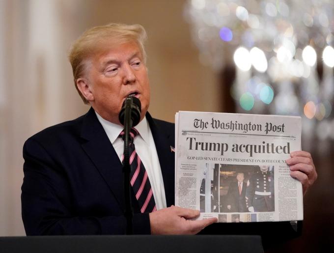 川普高舉《華盛頓郵報》報紙。(圖片:AFP)