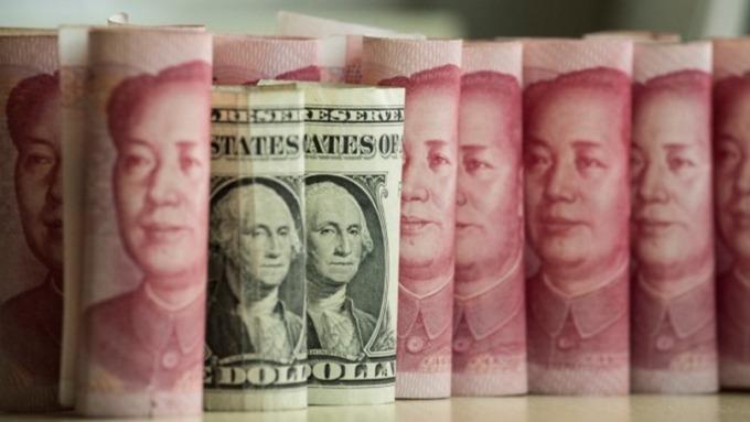 人民幣今晨收盤貶破7字頭 中間價跟進破7(圖片:AFP)