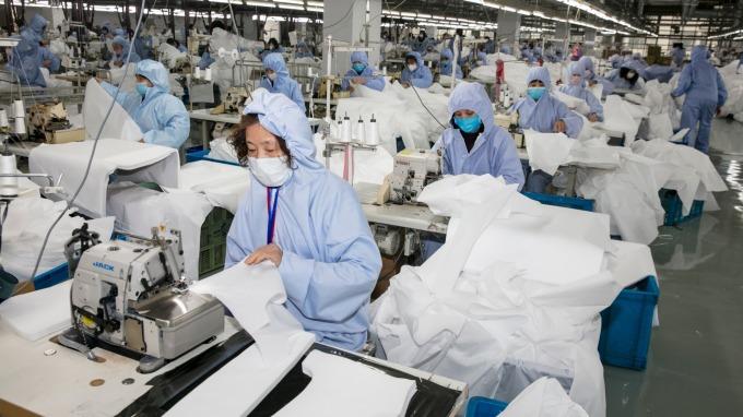因應防疫需求,儒鴻、聚陽協助趕工生產防護隔離衣。(圖:AFP)