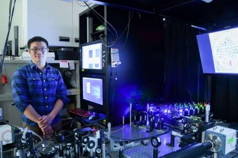 中研院應用科學研究中心陳壁彰助研究員與透化層光定位顯微鏡。 圖片來源│中研院秘書處