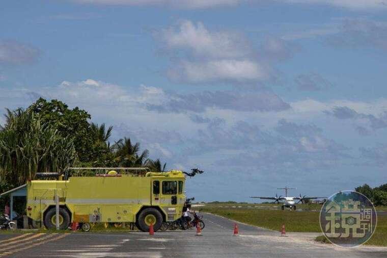 消防車鳴笛後,飛機降落於跑道上。
