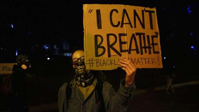 美示威抗議者高舉遭殺害的佛洛伊德生前求救語(圖片:AFP)