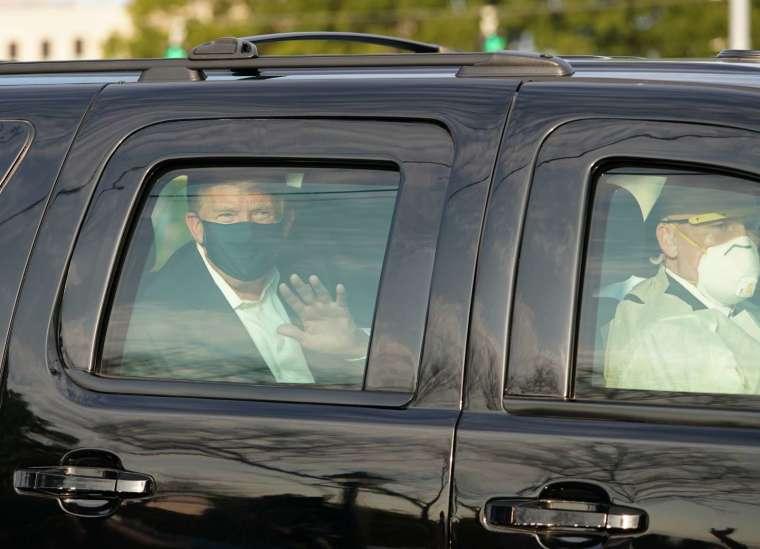 川普週日 (4 日) 短暫乘車離開軍醫院,向留守院外的支持者揮手致意 (圖片:AFP)