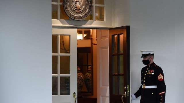 白宮西廂辦公室外一名海軍陸戰隊護衛戒備,顯示川普正在橢圓辦公室內。(圖:AFP)