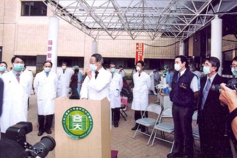 SARS 期間,李源德(講台後手握麥克風者)與應變團隊研擬縝密配套措施,疏散病人至其他院區,同時說服主管機關同意臺大醫院暫停急診,淨空消毒。(照片由院士李源德提供)