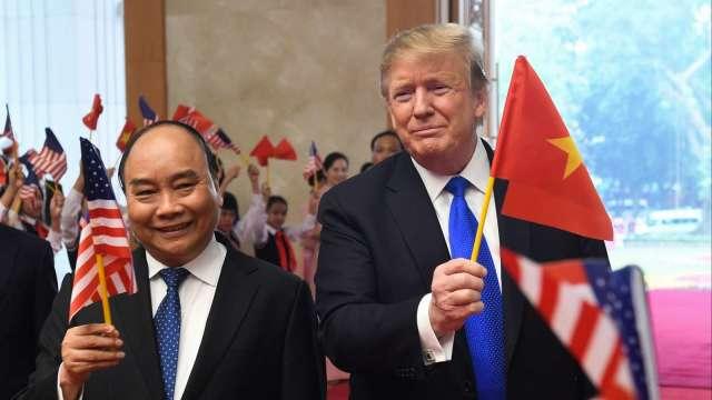 越南總理阮春福(左)和美國總統川普(右)互執彼國國旗。(圖片:AFP)