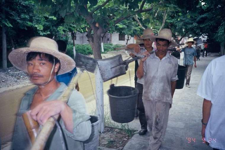 吳介民在廣東村落田調,一群民工從他身前經過,他順手拿起相機,按下快門的剎那,身前的工人正好抬起頭,直直望向鏡頭,留下這張意味深長的照片。民工是過去中國經濟成長的沉默貢獻與犧牲者,建築隊是最底層的民工,經常被拖欠工資、睡在工地。 圖│吳介民