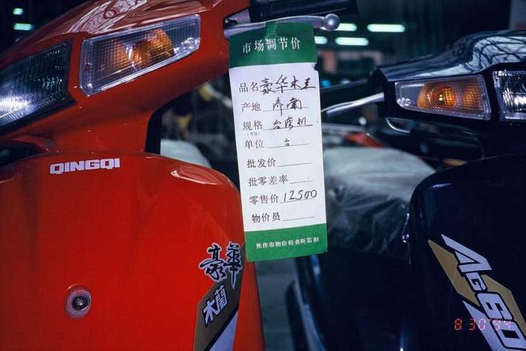 1994 年,河南省濟源市一家摩托車店的標示。明明是當地生產,卻被特別標註「台灣機」,而且一台摩托車要價 12500 元!一方面顯示當時台灣因素扮演的經濟影響力,同時這樣的高價品,必定也是飽賺「灰色收入」的幹部才買得起。 圖│吳介民