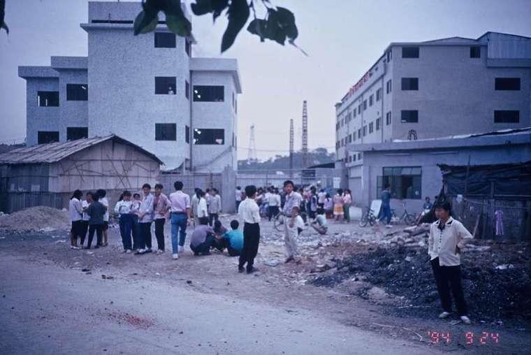 廣東珠三角工業區,常見大批民工站在廢棄物前休息。「廣東模式」是吳介民分析中國模式的原型,1978 年廣東成為中國「改革開放」先鋒,政府從內地省分的農村大量引入農民工(簡稱民工),持續提供勞動力。 圖│吳介民